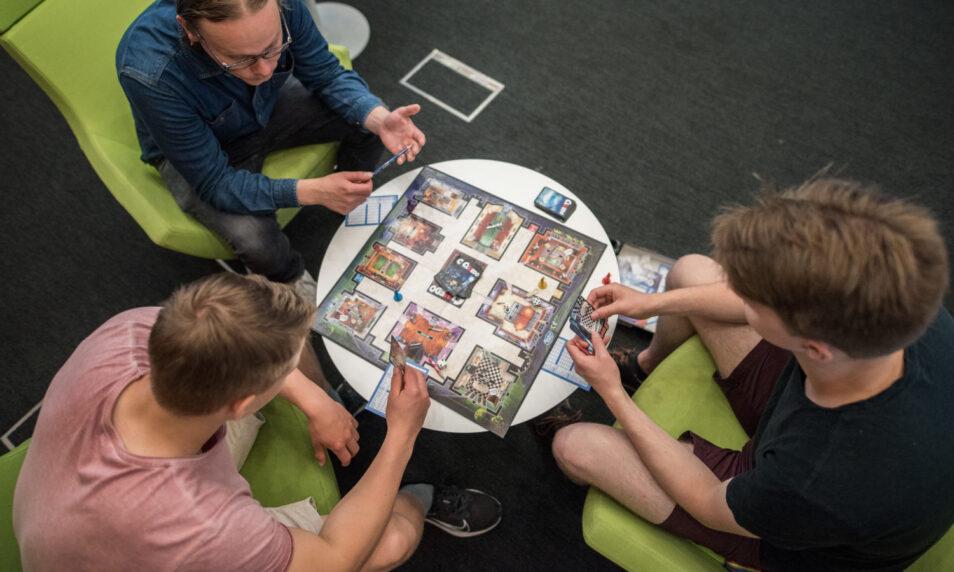 kolme ihmistä pöydän ympärillä pelaamassa lautapeliä